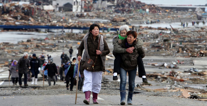 A woman carries an elderly woman on her back after the 2011 tsunami in Japan. Minami-Sanriku-cho, a town located in Miyagi Prefecture is unrecognizable. Credit: The Kahoku Shimpo.
